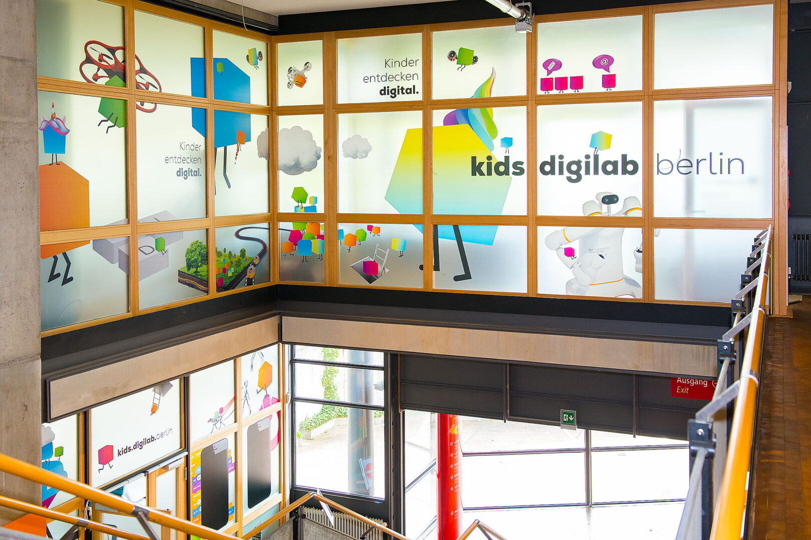 Ansicht von der Innentreppe auf Glasfassade der oberen Etage des kids.digilab und unteren Eingang des kids.digilab.
