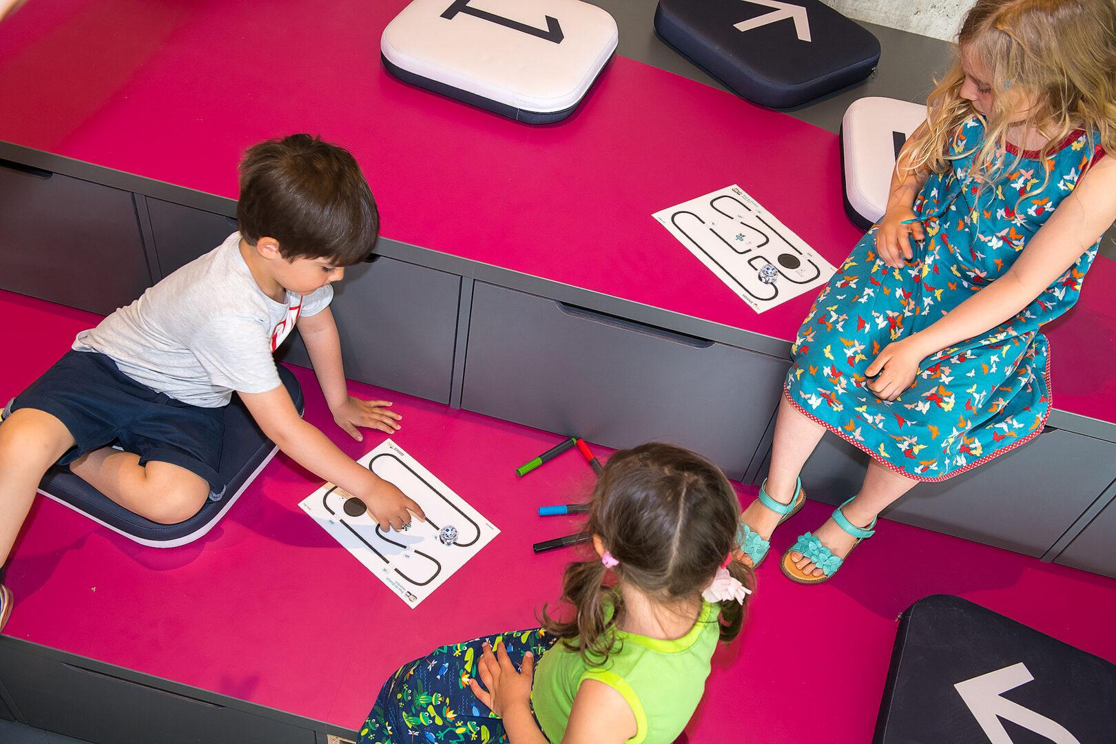 Ein kleiner Junge zeigt auf gemalte Linien, auf denen ein Robotik-Spielzeug entlangfährt, zwei Mädchen schauen zu.