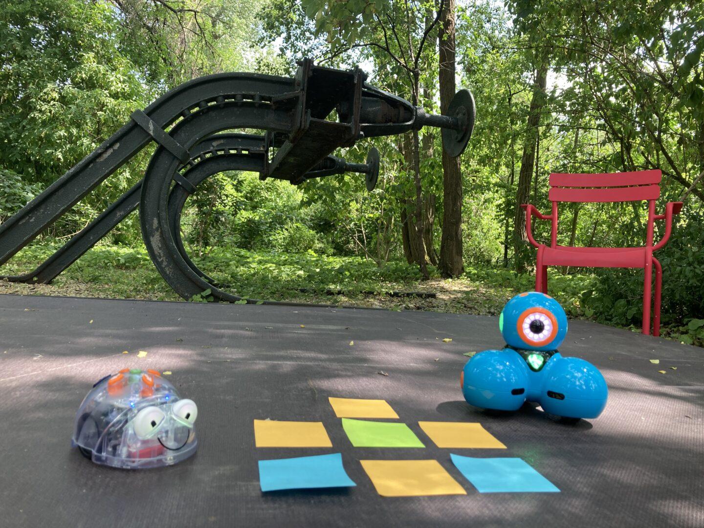 im Museumspark zwei Spielroboter auf einem grauen Podest mit Post-its, vor einem roten Gartenstuhl und einem schwarzen Eisengerüst