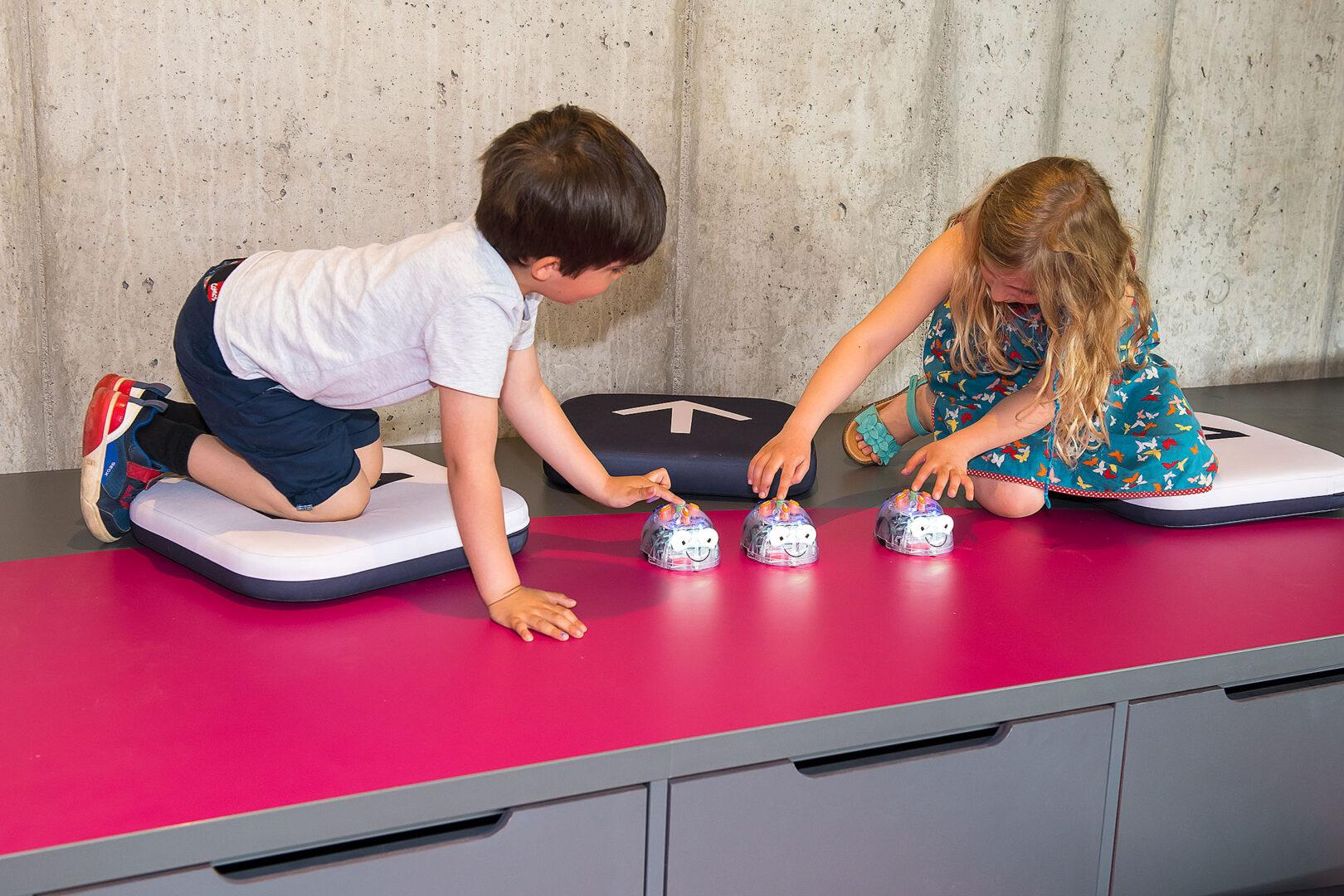 Zwei Kinder drücken die Startknöpfe mehrerer Robotik-Spielzeuge, die wie gläserne Mäuse aussehen.