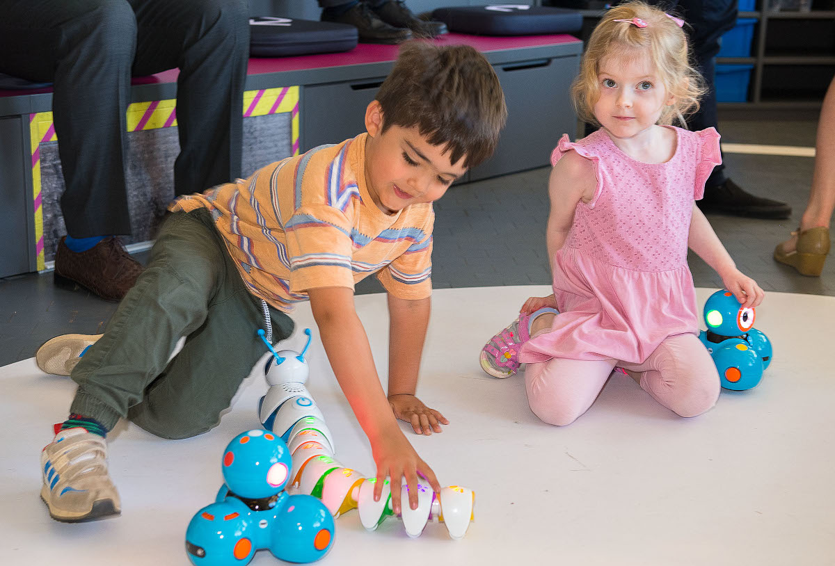Ein Junge spielt mit einem Raupen-Roboter. Naben ihm kniet ein Mädchen.